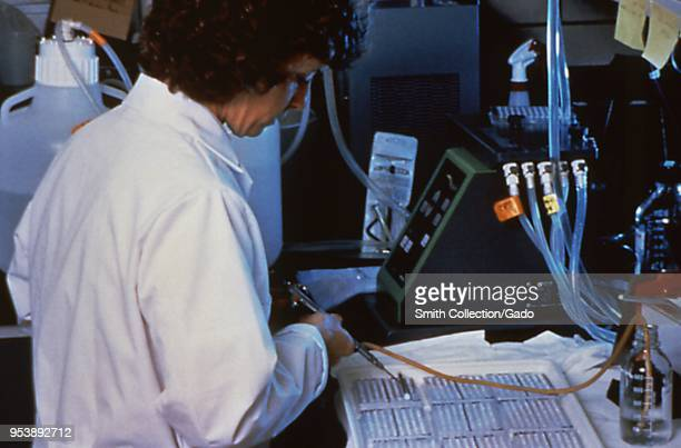 Centers for Disease Control Special Pathogens Branch scientist performing an EnzymeLinked ImmunoSorbent Assay test on suspected Hantavirus samples...