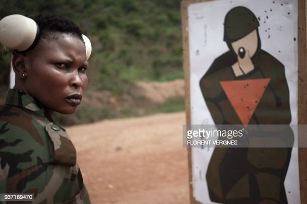 A Central African Armed Forces soldier looks at her target during a training with an assault rifle at Camp Kassai in Bangui on March 14 2018 At this...