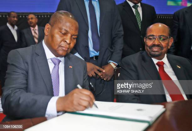 Central African president Faustin-Archange Touadera inks a peace deal next to Sudanese President Omar al-Bashir in Khartoum on February 05, 2019. -...