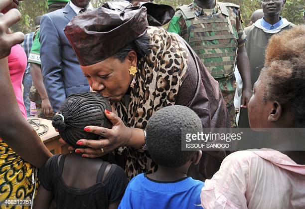 Central African Republic transitional President Catherine Samba-Panza kisses a young child during a visit to a camp for displaced civilians in Bangui...