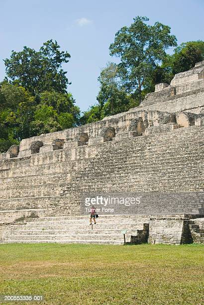 Central America, Belize, Caracol, man walking up steps of ruin