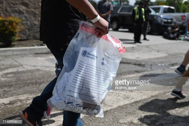 A Central American asylum seeker carries his belongings after he and about 40 others were released from US Border Patrol vans at the bus station by...