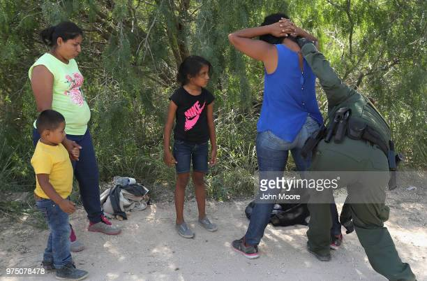 Central American asylum seekers are taken into custody by US Border Patrol agents on June 12 2018 near McAllen Texas The families were then sent to a...