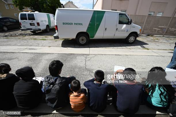 Central American asylum seekers sit outside the bus station in San Bernardino, California after they were released from three U.S. Border Patrol...