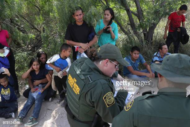 Central American asylum seekers wait as US Border Patrol agents take groups of them into custody on June 12 2018 near McAllen Texas The families were...