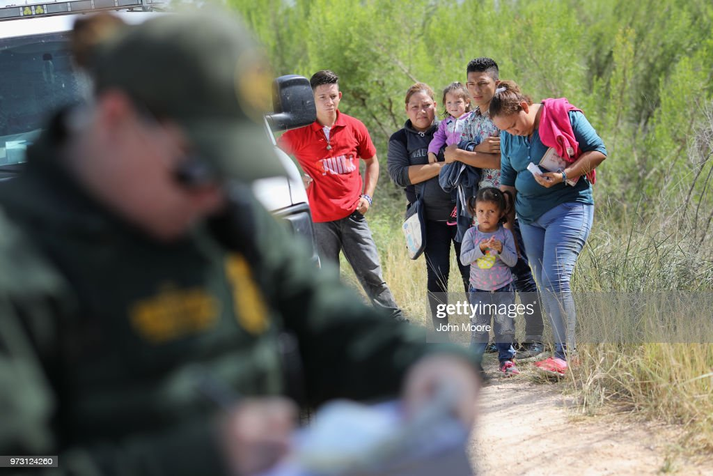 Central American asylum seekers wait as U.S. Border Patrol agents take groups of them into custody on June 12, 2018 near McAllen, Texas. The families were then sent to a U.S. Customs and Border Protection (CBP) processing center for possible separation. U.S. border authorities are executing the Trump administration's zero tolerance policy towards undocumented immigrants. U.S. Attorney General Jeff Sessions also said that domestic and gang violence in immigrants' country of origin would no longer qualify them for political-asylum status.