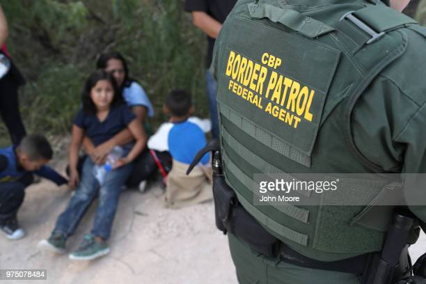 Central American asylum seekers wait as US Border Patrol agents take them into custody on June 12 2018 near McAllen Texas The families were then sent...