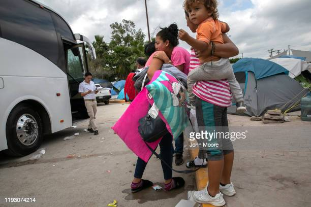 Central American families bid farewell to others boarding wait a bus back to their home countries from a camp for asylum seekers on December 08, 2019...