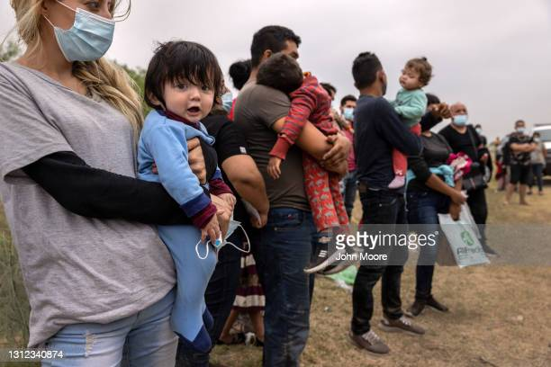 Central American families, including a mother and son from El Salvador board a U.S. Customs and Border Protection bus for transport to an immigrant...