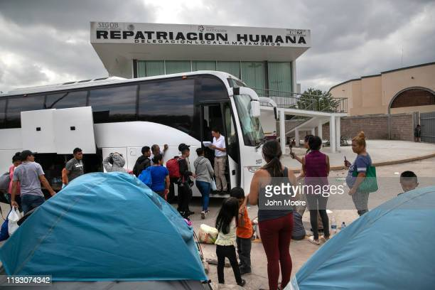 Central American families wait to board a bus back to their home countries from a camp for asylum seekers on December 08 2019 in the Mexican border...