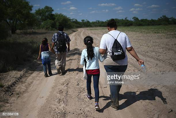 Central American immigrant families walk through the countryside after crossing from Mexico into the United States to seek asylum on April 14 2016 in...