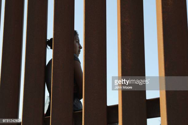 Central American immigrant stands at the USMexico border fence after crossing into Texas on June 12 2018 near Mission Texas US Customs and Border...