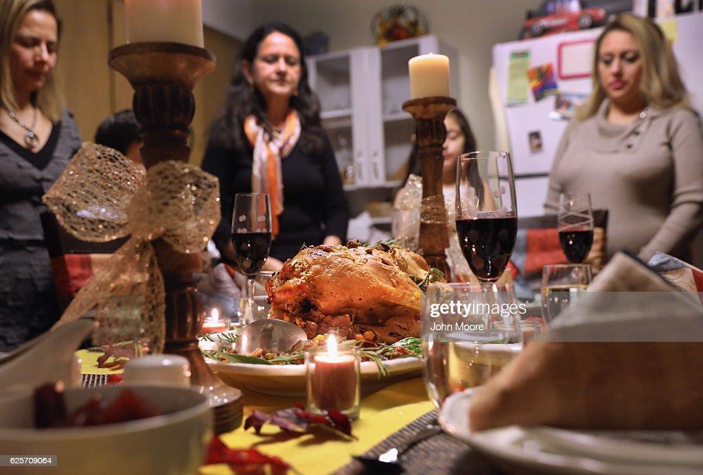 Central American immigrants and their families pray before Thanksgiving dinner on November 24, 2016 in Stamford, Connecticut. Family and friends, some of them U.S. citizens, others on work visas and some undocumented immigrants came together in an apartment to celebrate the American holiday with turkey and Latin American dishes. They expressed concern with the results of the U.S. Presidential election of president-elect Donald Trump, some saying their U.S.-born children fear the possibilty their parents will be deported after Trump's inauguration.