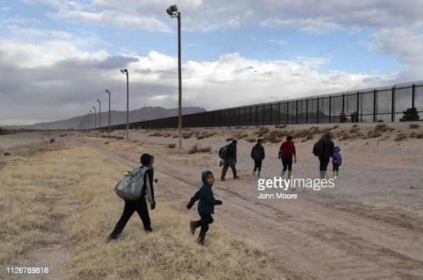 Central American immigrants approach the U.S.-Mexico border fence after crossing the Rio Grande from Mexico on February 01, 2019 in El Paso, Texas....