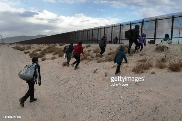 Central American immigrants approach the USMexico border fence after crossing the Rio Grande from Mexico on February 01 2019 in El Paso Texas The...