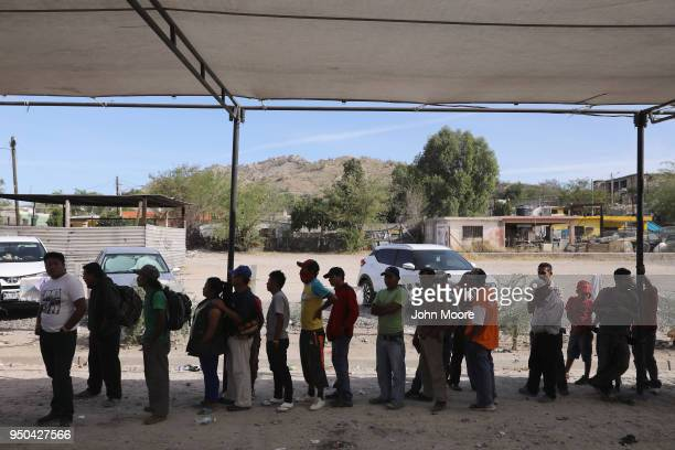 Central American immigrants part of an immigrant 'caravan' line up to eat before staging a protest against US President Donald Trump on April 23 2018...