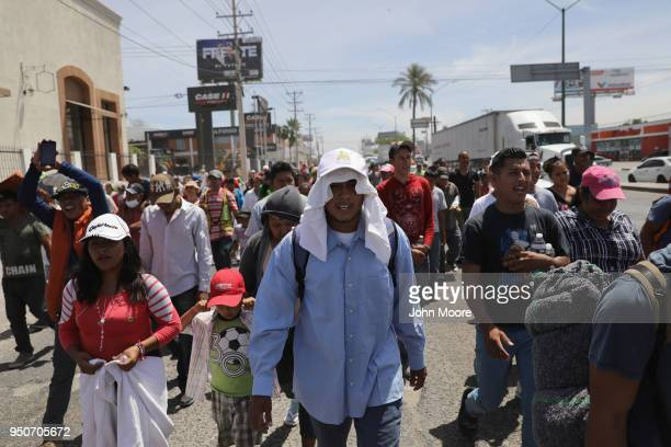 Central American immigrants part of an immigrant 'caravan' march in protest against US President Donald Trump on April 23 2018 in Hermosillo Mexico...