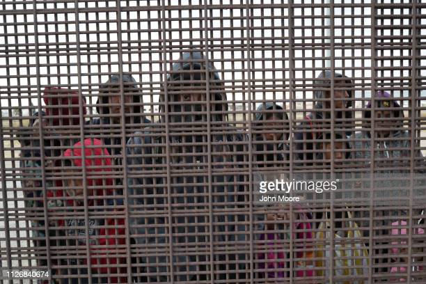 Central American immigrants stand at the USMexico border fence after crossing the Rio Grande from Mexico on February 01 2019 in El Paso Texas The...