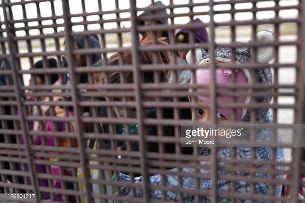 Central American immigrants stand at the USMexico border fence while crossing the border from Mexico on February 01 2019 in El Paso Texas The...