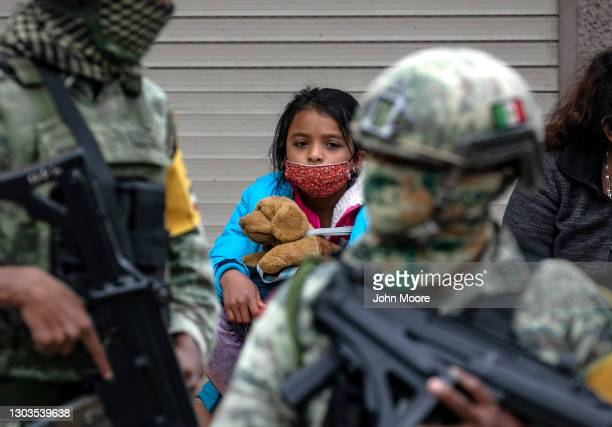Central American immigrants wait at migrant camp for entry into the United States as Mexican military police stand guard on February 22, 2021 in...