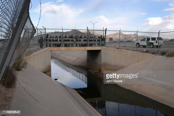 Central American immigrants wait to be taken into custody after crossing the Rio Grande from Mexico on February 01 2019 in El Paso Texas The migrants...