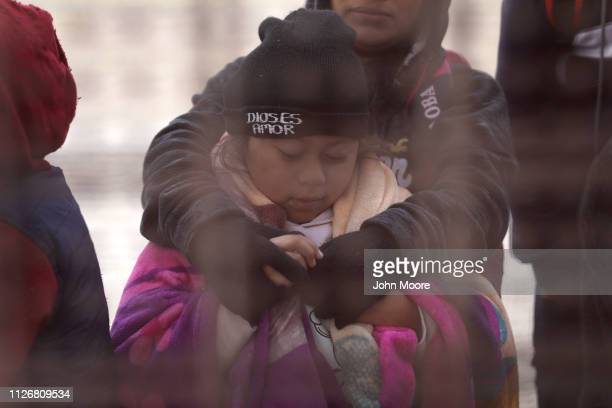 Central American immigrants wait to be taken into custody at the USMexico border fence after crossing the Rio Grande from Mexico on February 01 2019...