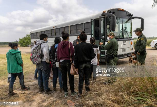 Central American immigrants wait to be transported to a processing center by U.S. Border Patrol agents near the border with Mexico on April 11, 2021...