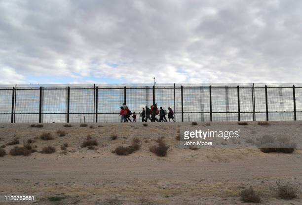 Central American immigrants walk along the USMexico border fence after crossing the Rio Grande from Mexico on February 01 2019 in El Paso Texas They...