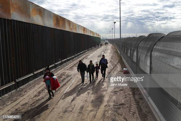 Central American immigrants walk between a Bollardstyle border fence left and the older 'legacy' fence after crossing the Rio Grande from Mexico on...