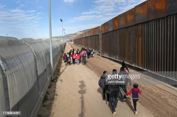 Central American immigrants walk between a Bollardstyle border fence right and the older legacy fence after crossing the Rio Grande from Mexico on...