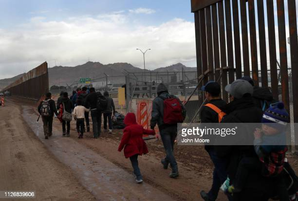 Central American immigrants walk between a gap in the border fence after crossing the Rio Grande from Mexico on February 01 2019 in El Paso Texas The...