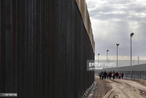 Central American immigrants walk between a newly built Bollardstyle border fence and the older legacy fence after crossing the Rio Grande from Mexico...