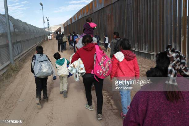 """Central American immigrants walk between a newly built Bollard-style border fence, right, and the older """"legacy"""" fence after crossing the Rio Grande..."""