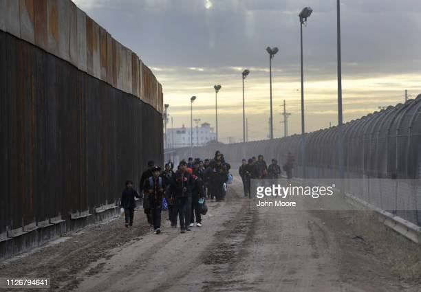 Central American immigrants walk between a newly built Bollardstyle border fence left and the older legacy fence after crossing the Rio Grande from...