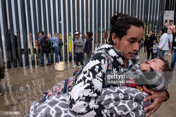 Central American migrant carries a child after a Border Patrol sprayed them while trying to cross the USMexico border fence from Tijuana to San Diego...