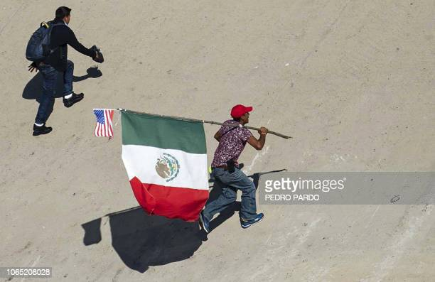 A Central American migrant carrying a Mexican and a US flag crosses the almost dry riverbed of the Tijuana River in an attempt to get to El Chaparral...
