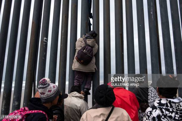 A Central American migrant climbs down the USMexico border fence from Tijuana to San Diego as seen from Playas de Tijuana in Baja California state...