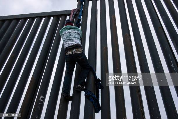 Central American migrant climbs down the USMexico border fence from Tijuana to San Diego as seen from Playas de Tijuana in Baja California state...