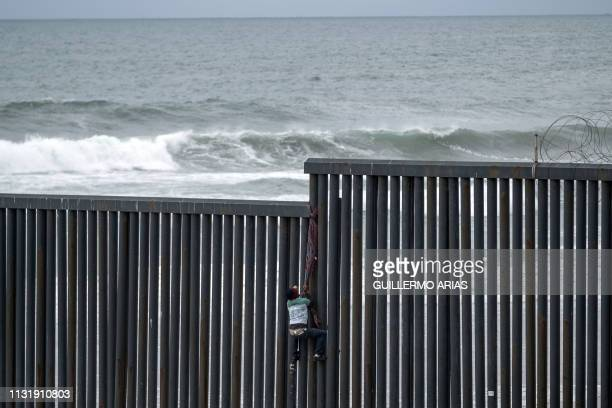 Central American migrant climbs the USMexico border fence from Tijuana to San Diego as seen from Playas de Tijuana in Baja California state Mexico on...