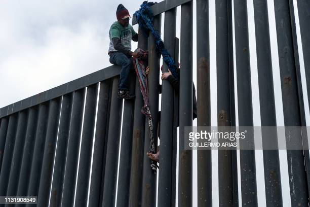 A Central American migrant crosses the USMexico border fence from Tijuana to San Diego seen from Playas de Tijuana in Baja California state Mexico on...