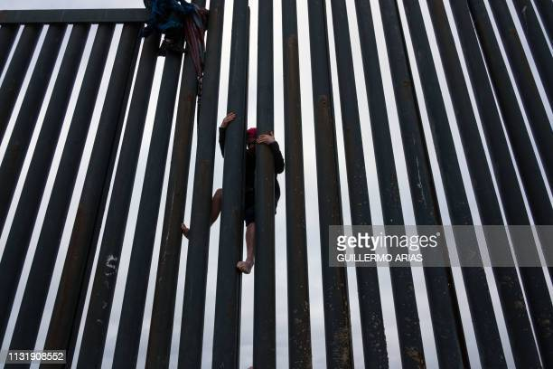 Central American migrant crosses the USMexico border fence from Tijuana to San Diego seen from Playas de Tijuana in Baja California state Mexico on...