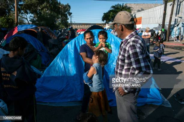 A Central American migrant family travelling in a caravan stand by a tent at a makeshift camp backdropped by the USMexico border fence in a street...