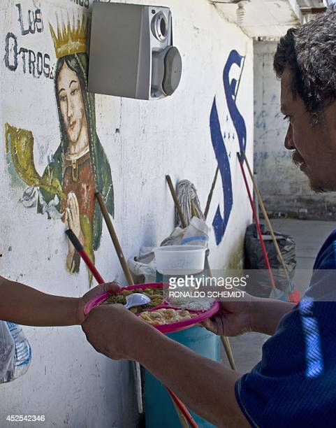 A Central American migrant gets food at the Sagrada Familia shelter as he waits for the socalled La Bestia cargo train in an attempt to reach the US...