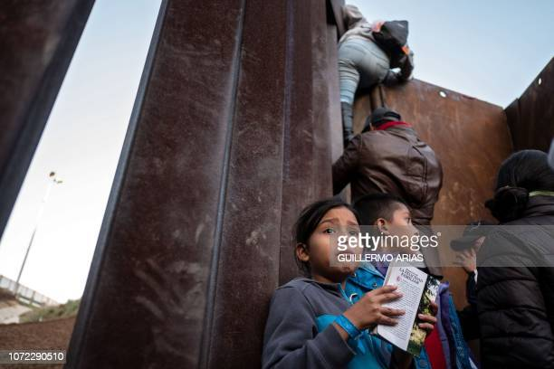 A Central American migrant girl holds a book as other migrants travelling in a caravan climb the MexicoUS border fence in an attempt to cross to San...