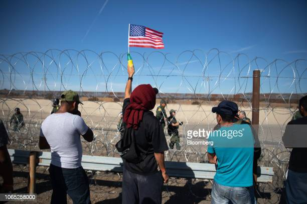 A Central American migrant holds an American flag in front of barbed wire along the US and Mexico border in Tijuana Mexico on Sunday Nov 25 2018 US...