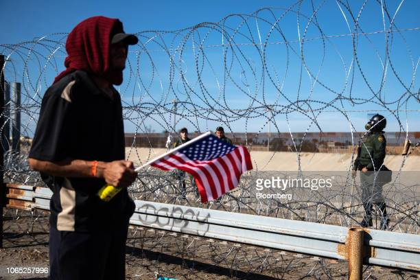 A Central American migrant holds an American flag near barbed wire border fence along the the US and Mexico border in Tijuana Mexico on Sunday Nov 25...