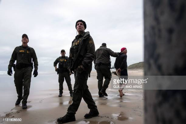 Central American migrant is taken in custody by Border Patrol after crossing the USMexico border fence from Tijuana to San Diego as seen from Playas...