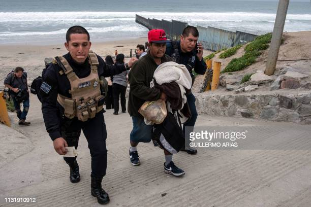 Central American migrant is taken into custody by Tijuana police after migrants faced US Border Patrol agents while trying to cross the USMexico...