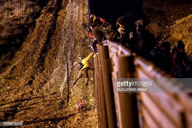 Central American migrant jumps over the USMexico border fence from Tijuana to San Diego in the US as seen from Tijuana Baja California state Mexico...
