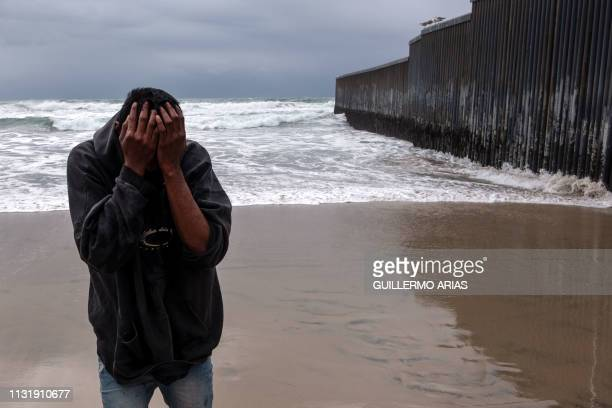 A Central American migrant reacts after being sprayed while trying to cross the USMexico border fence from Tijuana to San Diego as seen from Playas...